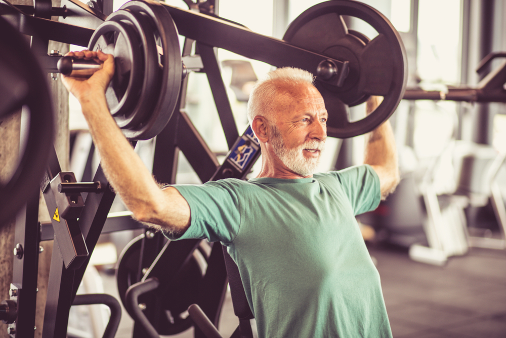 Senior man lifting weights at the gym