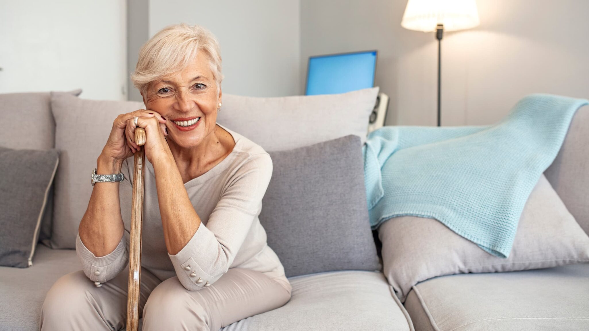 Happy older woman sitting on a couch and resting on a cane.
