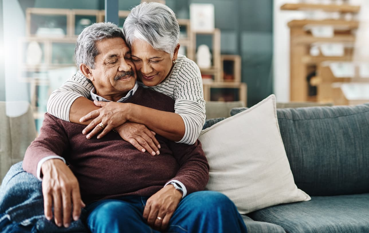 Elderly woman hugging her husband who's on the couch at home.