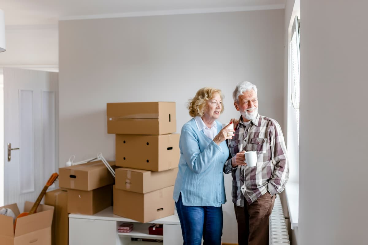 Older couple standing in home with cardboard moving boxes behind them.