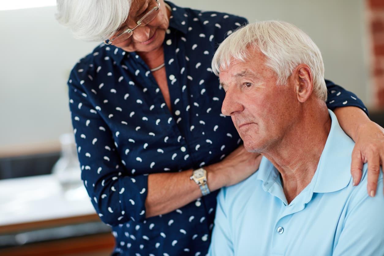 Older woman comforts her husband.