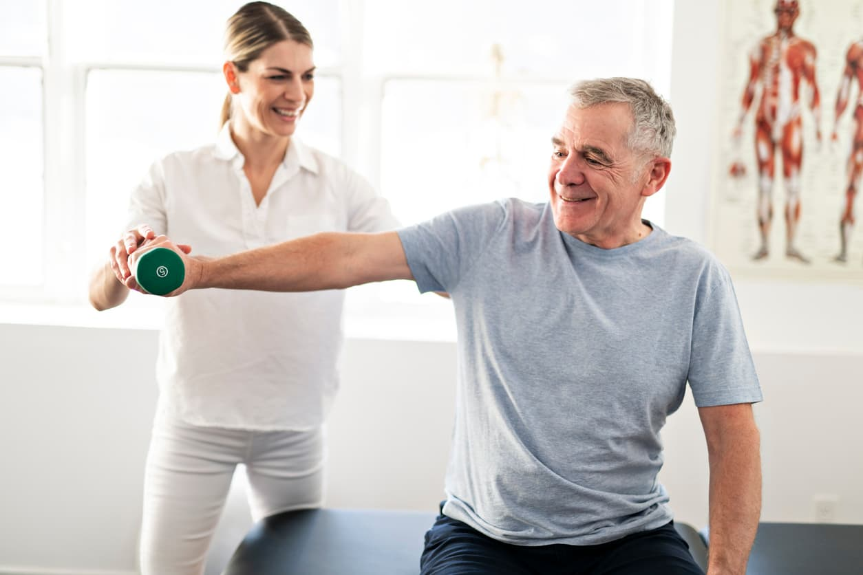 Modern rehabilitation physiotherapy worker with senior patient.