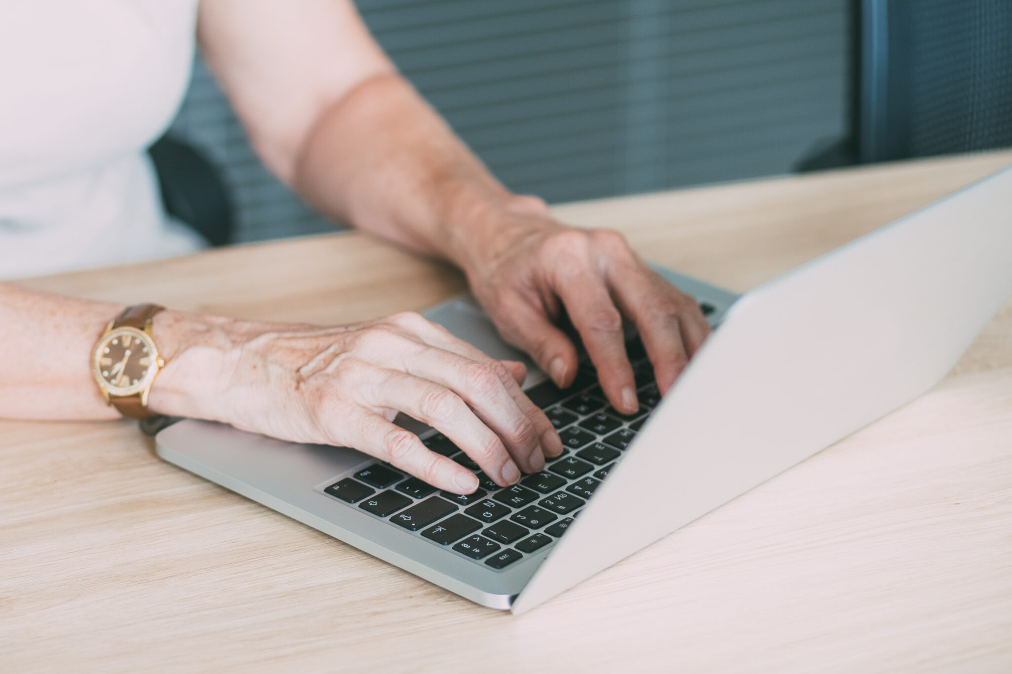 A closeup of a pair of hands typing on a laptop